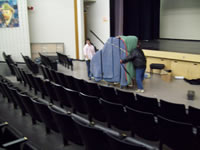 grand piano wheeled into auditorium